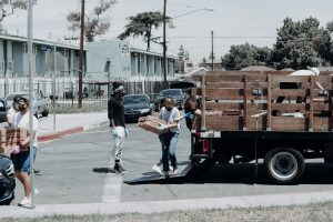 disaster relief man in black jacket and blue denim jeans standing beside brown wooden box trailer during daytime