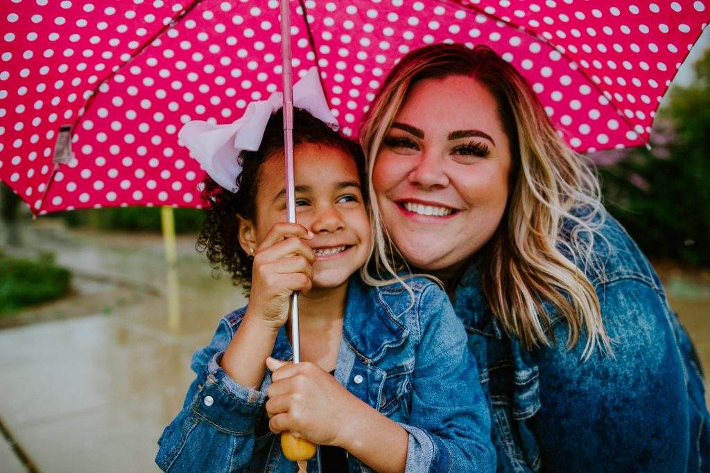 Adoption Travel woman in blue denim jacket holding umbrella smiling