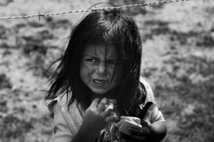 ecuador mission trip girl holding hair comb behind barbed wire